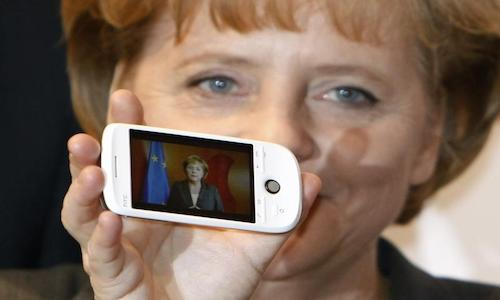 A photo from 2009 shows German Chancellor Angela Merkel holding a cellphone with a photo of her on the screen.